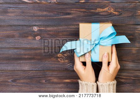 Woman hands give wrapped valentine or other holiday handmade present in paper with red blue and green ribbon. Present box decoration of gift on white wooden table top view with copy space.