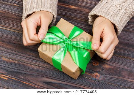 Girl tying a simple green bow on a gift box. Wrapped in plain craft paper and Blue ribbon. Finishing touche.