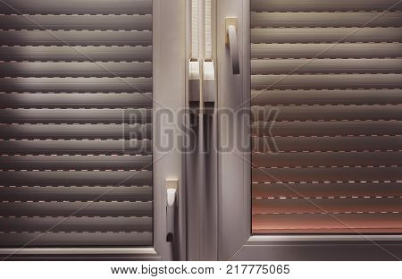 Closed aluminum blinds view from inside, accentuated shapes with light.