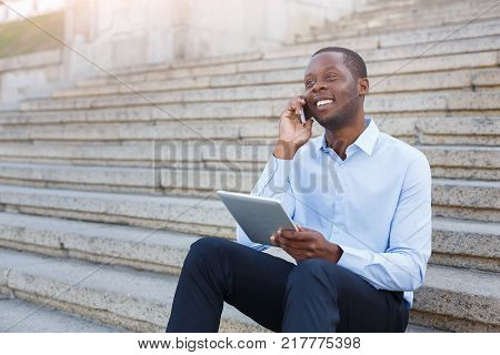 Happy black businessman working on tablet. African-american insuranse agent checking email on digital device, talking on mobile, sitting on the stairs outdoors in urban area