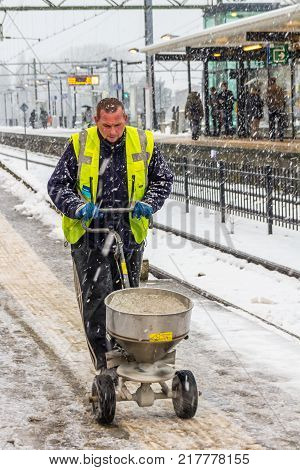 Laan van NOI The Hague the Netherlands - December 11 2017: municipal worker spreading grit on train station platform