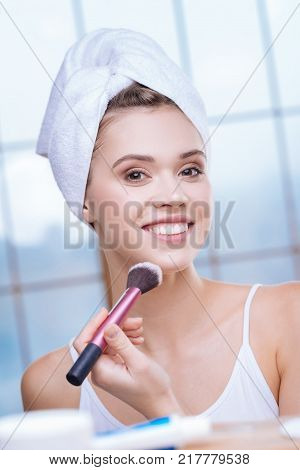 Always beautiful. Attractive upbeat woman in a white tank top drying her hair with a towel turban and applying some powder to her jaw line