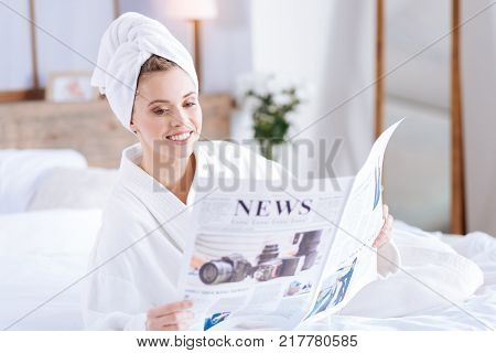 Tracking world events. Charming young woman lying on the bed and reading articles in the newspaper while wearing a towel turban and a white bathrobe