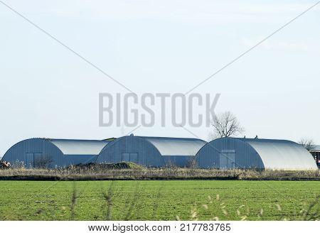 Three hangars in the field. Hangars from galvanized iron