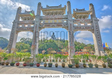 Hong Kong, China - December 5, 2016: Scenic gateway in a sunny day of Po Lin Monastery and the Big Buddha on background, icon and symbol of Lantau Island, popular tourist destination of Hong Kong, China.