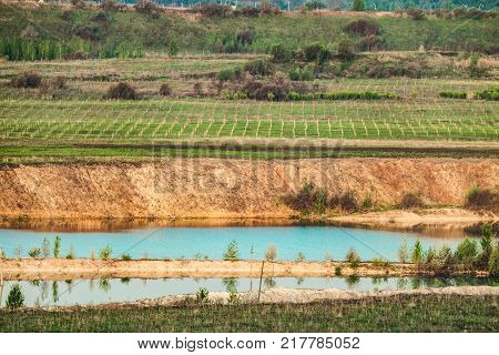 Non-ecological landscape with technogenic erosion of soils. A strip of agrotechnical measures to protect the soil from destruction. Lake is chalk and clay quarry.