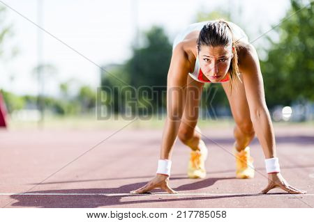 Beautiful female sprinter getting ready for the run during summer poster