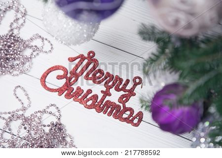 Merry christmas red gleaming inscription with a chain of pink beads and unfocused fir tree branches with baubles on a white wooden background. Close up poster