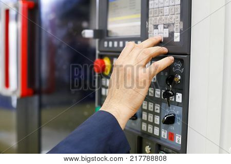 Operator working with CNC machining center using control panel. Selective focus.