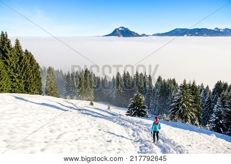 Healthy woman cross country running in amazing winter mountain landscape. Female trail runner jogging exercising outdoors. Allgau, Bavaria, Germany.