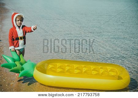 Winter holiday vacation. Xmas party celebration childhood. New year small boy at beach. Christmas happy child with pineapple mattress in water. Santa claus kid in red Christmas costume.