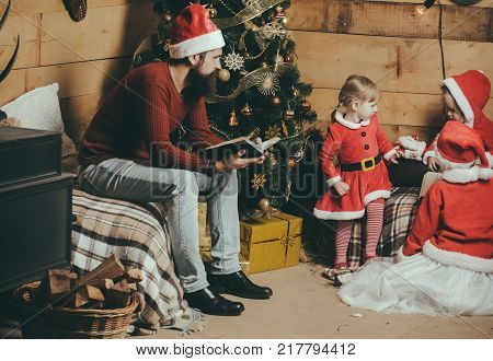 Christmas happy children and father read book. Winter holiday and vacation. New year small girl and man fairytale. Xmas celebration fathers day. Santa claus kid and bearded man at Christmas tree.