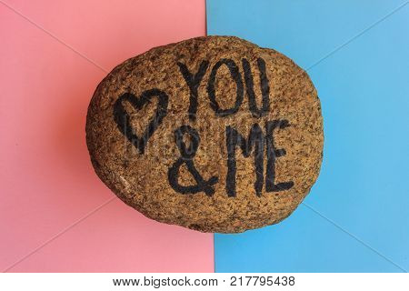 the english  writing you and me with a heart drawn on a stone, the writing you and me with a heart drawn on a stone indicates the love promise of two lovers