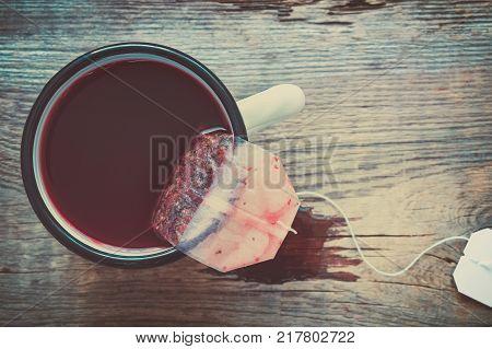 Tea bag of red fruit and berries tea in brewing tea in enameled mug.