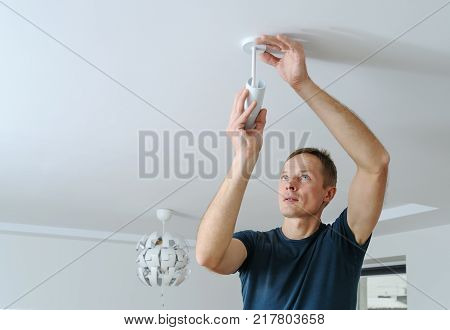 Installing a lamp at home. The man is fixing the spotlight to the ceiling.