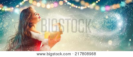 Christmas Winter Woman opening magic Christmas Gift box. Fairy. Beautiful New Year and Christmas scene, Beauty Fashion Model Girl With Present Box in hands smiling. Holiday Magic stars, light, garland