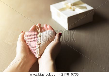 Woman hand holding a gift box. A gift from a heart charity case and thoughtful presents
