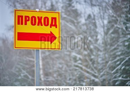 Yellow direction sign with red word and arrow on winter forest background