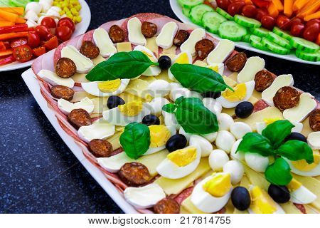 Buffet catering food with basil egg mozarella sausage ham olive carrot tomatoes and others vegatable arangement on table.
