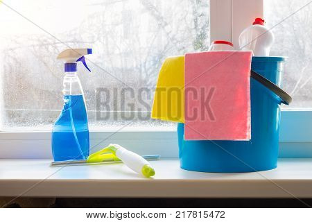Bucket spray and squeegee for window cleaning on the window sill. The concept of cleaning Windows.
