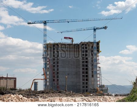 Building Construction with crane in the day with clouds