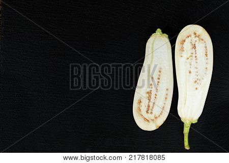 White hite eggplant on a black stone surface. The half eggplant. Top view. Copy space.