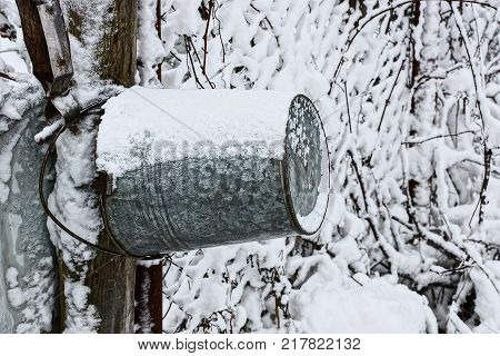 a gray iron bucket hangs on a wooden pole in the snow near the well