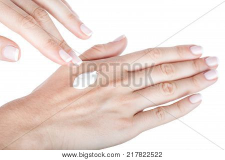 Body Care. Applying hand moisturiser cream on female hands, closeup isolated on white