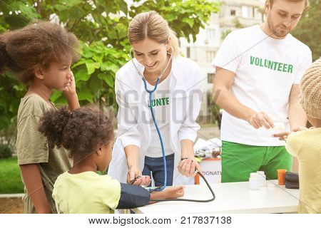 Volunteer doctor measuring blood pressure of poor African child outdoors