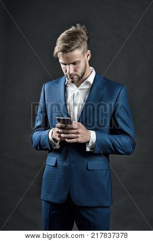 Business communication and modern life. Manager with beard on serious face hold phone. Man in formal outfit with mobile phone. digital marketing and new technology. Businessman or ceo fashion.