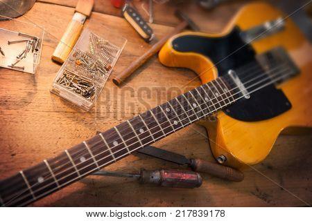 Guitar repair workbench. Vintage electric guitar on a guitar repair work shop. Single cutaway electric guitar, amber color.