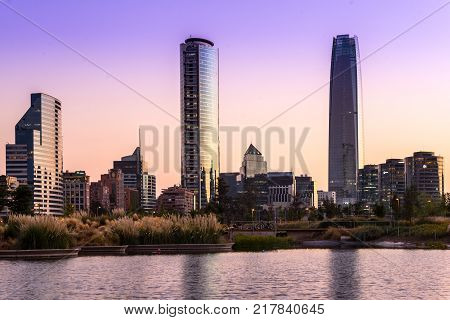 Santiago Region Metropolitana Chile - February 13 2017: Pond at Parque Bicentanario a park in the wealthy district of Vitacura with the skyline of the modern buildings at the financial district populary know as Sanhattan.