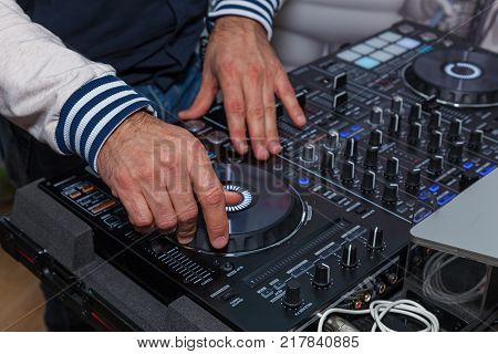 The DJ's hands on the music console. DJ console cd mp4 deejay mixing desk music party in nightclub. DJ console for experiments with music
