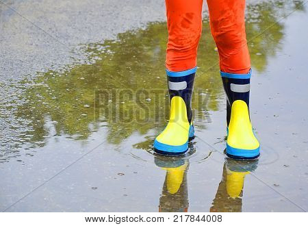 child standing in a puddle shod in rubber boots