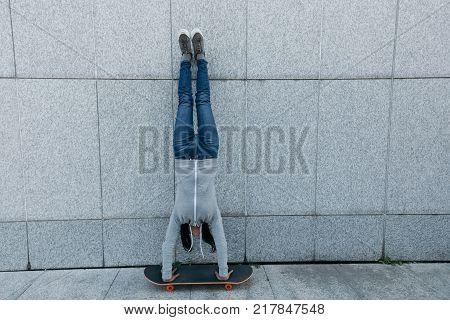 female skateboarder doing a handstand on skateboard against wall