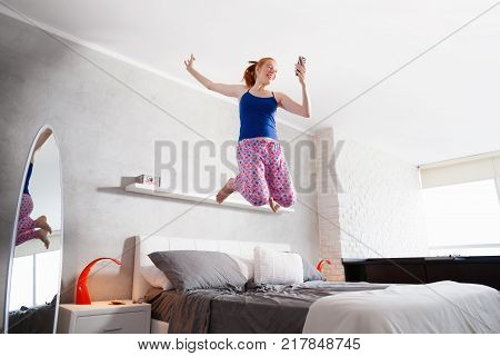 Happy young latina woman jumping mid air on bed, hispanic girl smiling and laughing in bedroom after reading good news on mobile phone.
