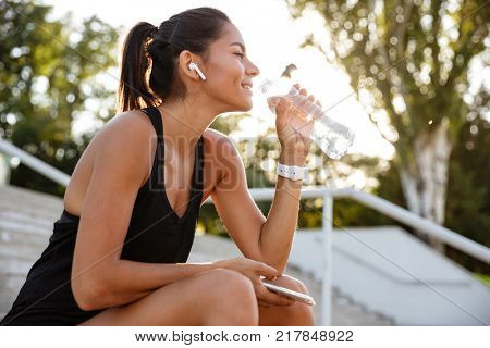 Portrait of a smiling fitness girl in earphones sitting on stairs outdoors with mobile phone and drinking water