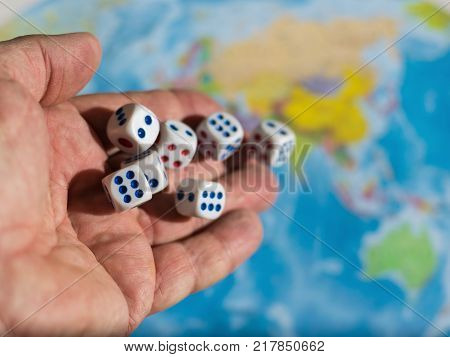 Male hand throwing dice on the table with a world map and money. The concept of ownership of the world. World order. The control population. poster