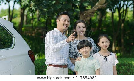 portrait of Chinese parents and kids standing outdoors beside car and smiling in direction father pointing