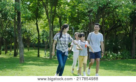 Chinese family smiling & walking together in park