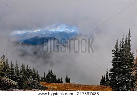 North Cascades landscape. Early winter scene in Cascade Mountains with trees beautiful view of snow covered mountains and autumn colours near Seattle. Washington. United States.