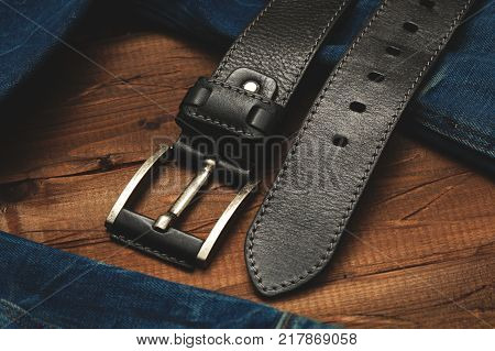 black leather belt with buckle for men on wooden background