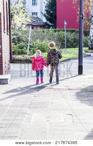 Brother and sister walking hand in hand in the streets of the city