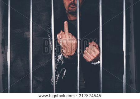 Handcuffed man behind prison bars giving middle finger as rude hand gesture. Arrested criminal male person imprisoned.