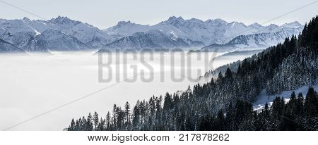 Wooded mountain slope and mountain range in low lying valley fog with silhouettes of evergreen conifers shrouded in mist. Scenic snowy winter landscape in Alps, Bavaria, Germany.