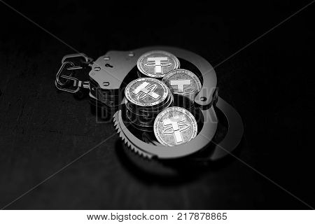 Piles of silver Tether coins in handcuffs as becomes very untrustworthy and shady concept. 3D rendering