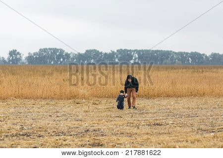Happy young father and son playing together and having fun in the autumn field. Family, child, fatherhood and nature concept.