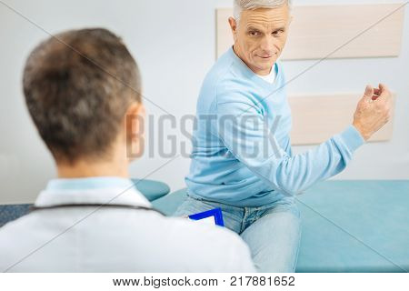 Look at it. Positive pleasant aged man sitting opposite his doctor and showing his hand while having a medical checkup