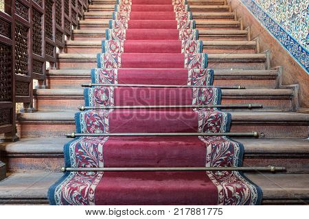 Cairo, Egypt - December 2, 2017: Front view of old ascending wooden stairs with ornate red carpet and wooden balustrade, Manial Palace of Prince Mohamed Ali