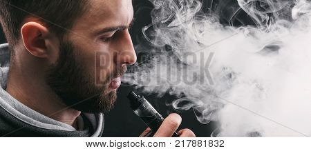 Man with vaping mod exhaling steam at black studio background. Bearded guy smoking e-cigarette to quit tobacco. Vapor and alternative nicotine free smoking concept, closeup